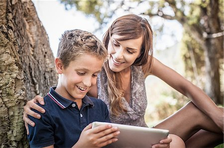 Mother and son looking at digital tablet in holiday home garden, Capoterra, Sardinia, Italy Stock Photo - Premium Royalty-Free, Code: 649-07760957