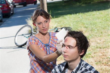 dangerous accident - Woman cleaning man with bleeding forehead Stock Photo - Premium Royalty-Free, Code: 649-07760997