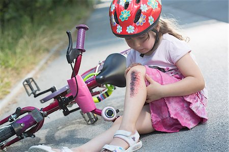 Young girl with injured leg sitting on road with bicycle Stock Photo - Premium Royalty-Free, Code: 649-07760998