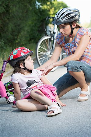 Mother caring for daughter fallen off bicycle Stock Photo - Premium Royalty-Free, Code: 649-07760999