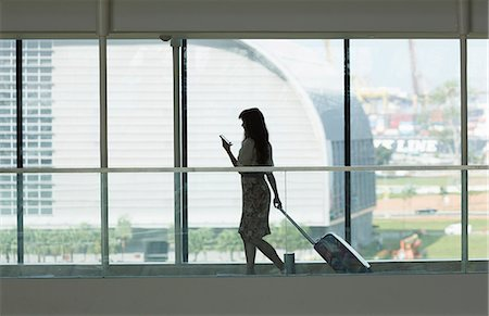 Young woman using smartphone and pulling suitcase in airport Stock Photo - Premium Royalty-Free, Code: 649-07761008