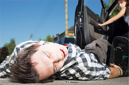 dangerous accident - Young man hit by car lying on road Stock Photo - Premium Royalty-Free, Code: 649-07761002