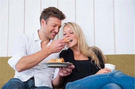 Couple sharing croissants on sitting room sofa Stock Photo - Premium Royalty-Free, Code: 649-07761065