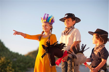 dress up girl - Three children dressed as native american and cowboys pointing from sand dunes Stock Photo - Premium Royalty-Free, Code: 649-07761115