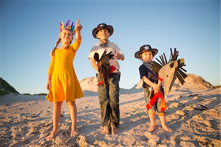 Sister and brothers dressed as native american and cowboys pointing from sand dunes Stock Photo - Premium Royalty-Free, Code: 649-07761111