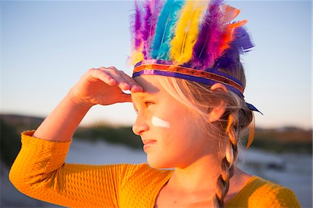 Close up of girl dressed as native american in feather headdress with hand shading eyes Stock Photo - Premium Royalty-Free, Code: 649-07761112