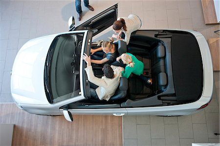 Overhead view of family trying out convertible car in car dealership Stock Photo - Premium Royalty-Free, Code: 649-07761179