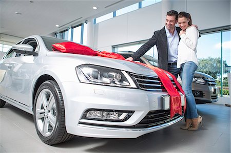 Man looking at new car with red bow with girlfriend in car dealership Stock Photo - Premium Royalty-Free, Code: 649-07761171