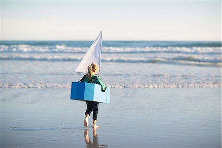 Girl running with toy boat into sea Stock Photo - Premium Royalty-Free, Code: 649-07761212