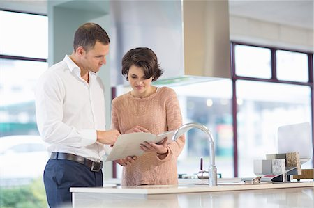 Female customer and salesman looking at brochure in kitchen showroom Stock Photo - Premium Royalty-Free, Code: 649-07761238