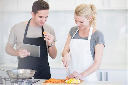 Couple chopping and tasting sliced vegetables in kitchen Stock Photo - Premium Royalty-Free, Code: 649-07761246