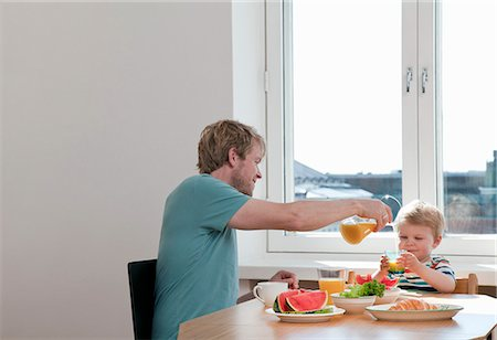 Father and toddler son having breakfast at kitchen table Stock Photo - Premium Royalty-Free, Code: 649-07761253