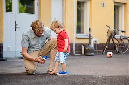 Father giving toddler son a hand to put on trainer in garden Stock Photo - Premium Royalty-Free, Code: 649-07761262