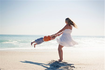 Mid adult mother swinging young son by hands on beach, Cape Town, Western Cape, South Africa Stock Photo - Premium Royalty-Free, Code: 649-07804096