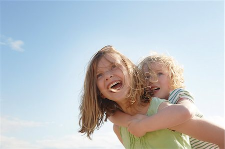 sister - Low angle view of girl giving sister piggy back at coast Stock Photo - Premium Royalty-Free, Code: 649-07804118
