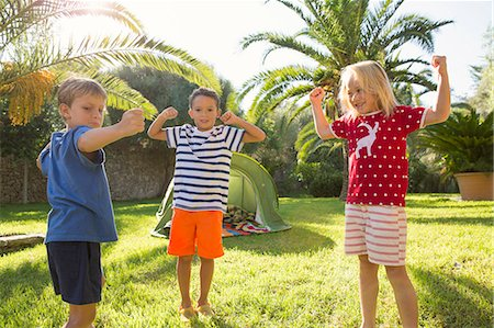 Three children in garden flexing muscles Stock Photo - Premium Royalty-Free, Code: 649-07804161