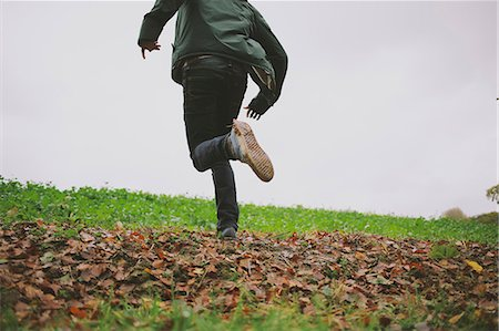 running away scared - Cropped shot of young man running in field Stock Photo - Premium Royalty-Free, Code: 649-07804189