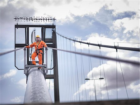 Bridge worker on cable of suspension bridge. The Humber Bridge, UK was built in 1981 and at the time was the world's largest single-span suspension bridge Stock Photo - Premium Royalty-Free, Code: 649-07804215