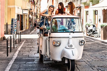 Three young women standing up in open back seat of Italian taxi, Cagliari, Sardinia, Italy Stock Photo - Premium Royalty-Free, Code: 649-07804268