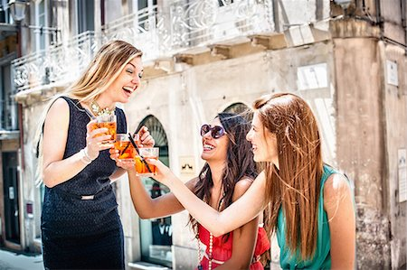 Three young fashionable female friends toasting with cocktails at sidewalk cafe, Cagliari, Sardinia, Italy Foto de stock - Sin royalties Premium, Código: 649-07804279