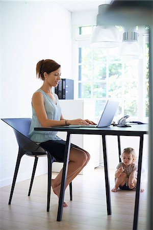Mid adult mother typing on laptop with toddler daughter under the table Stock Photo - Premium Royalty-Free, Code: 649-07804299