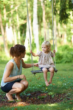 Mid adult mother and toddler daughter playing on garden swing Stock Photo - Premium Royalty-Free, Code: 649-07804290