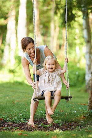 Mid adult mother pushing toddler daughter on garden swing Stock Photo - Premium Royalty-Free, Code: 649-07804293