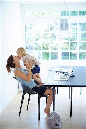 daughter kissing mother - Mid adult woman holding up and kissing toddler daughter Stock Photo - Premium Royalty-Free, Code: 649-07804305