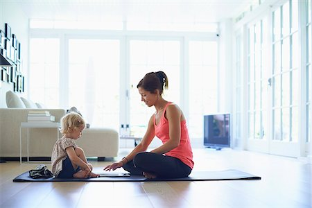 Mid adult mother and toddler daughter practicing yoga in living room Stock Photo - Premium Royalty-Free, Code: 649-07804309