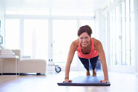 stretching (people exercising) - Mid adult woman doing press ups in living room Stock Photo - Premium Royalty-Free, Code: 649-07804315