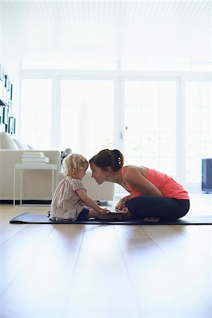 Mid adult mother and toddler daughter practicing lotus position in living room Stock Photo - Premium Royalty-Free, Code: 649-07804310