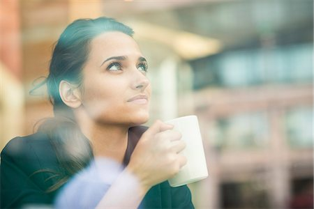 Young businesswoman drinking coffee and looking out of cafe window, London, UK Stock Photo - Premium Royalty-Free, Code: 649-07804321