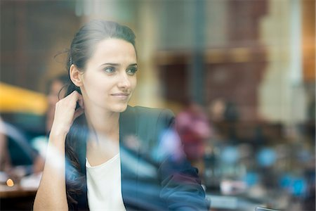 Young businesswoman looking out of cafe window, London, UK Stock Photo - Premium Royalty-Free, Code: 649-07804322