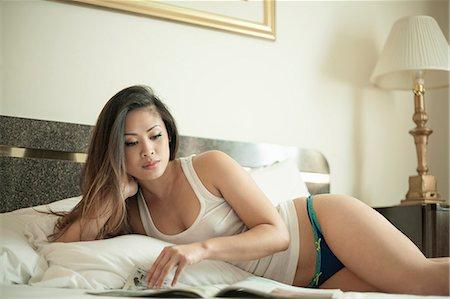 Woman lying on bed reading magazine Stock Photo - Premium Royalty-Free, Code: 649-07804346