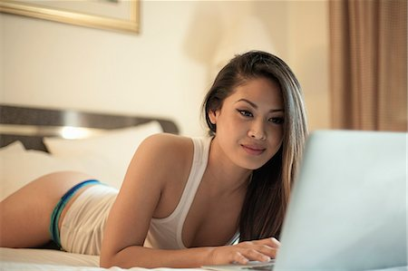 Attractive woman lying on bed, using laptop Stock Photo - Premium Royalty-Free, Code: 649-07804357