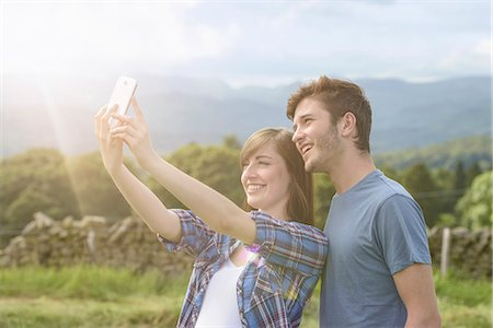 Young couple taking self portrait on mobile phone in countryside under sunny sky Stock Photo - Premium Royalty-Free, Code: 649-07804416