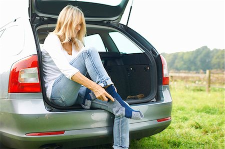 Woman sitting at rear of car putting on socks Stock Photo - Premium Royalty-Free, Code: 649-07804578