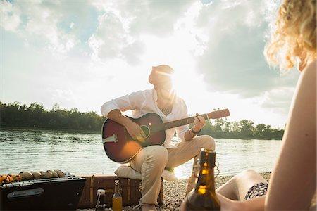 Young man sitting by lake playing guitar Stock Photo - Premium Royalty-Free, Code: 649-07804731