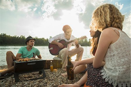 Young man sitting by lake with friends playing guitar Stock Photo - Premium Royalty-Free, Code: 649-07804732