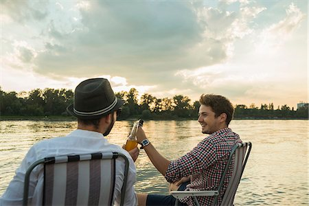 Young men toasting with beer bottles by lake Stock Photo - Premium Royalty-Free, Code: 649-07804744