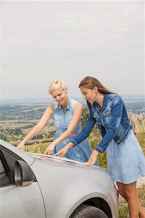day - Friends reading map on bonnet of car, Roznov, Czech Republic Stock Photo - Premium Royalty-Free, Code: 649-07804887