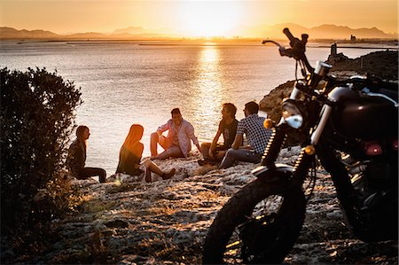 road trip - Five motorcycling friends taking a break on coast at sunset, Cagliari, Sardinia, Italy Stock Photo - Premium Royalty-Free, Code: 649-07803248