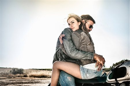 rustique - Young couple hugging and straddling motorcycle on arid plain, Cagliari, Sardinia, Italy Photographie de stock - Premium Libres de Droits, Code: 649-07803243