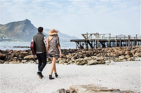 Young couple strolling on beach carrying guitar, Cape Town, Western Cape, South Africa Stock Photo - Premium Royalty-Free, Code: 649-07803284