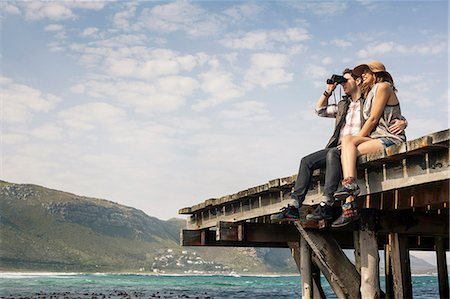 Young couple sitting on edge of old pier looking through binoculars, Cape Town, Western Cape, South Africa Stock Photo - Premium Royalty-Free, Code: 649-07803295