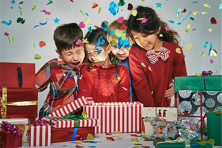 Surprised brothers and sisters unwrapping glowing christmas gift box with exploding confetti Stock Photo - Premium Royalty-Free, Code: 649-07803309