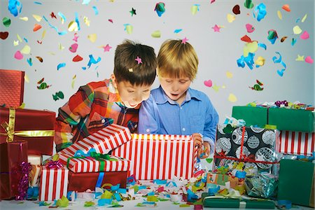 Two brothers open mouthed on unwrapping glowing christmas gift box with exploding confetti Foto de stock - Sin royalties Premium, Código: 649-07803310
