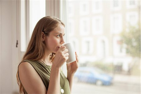 Young woman drinking coffee and gazing through sitting room window Stock Photo - Premium Royalty-Free, Code: 649-07803358