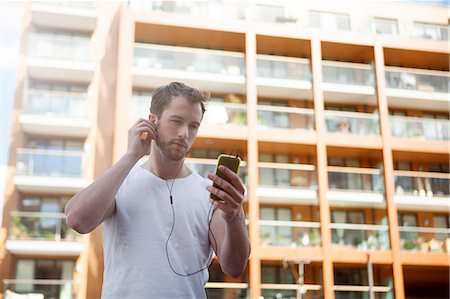 Man listening to music on headphones, building in background Stock Photo - Premium Royalty-Free, Code: 649-07803406