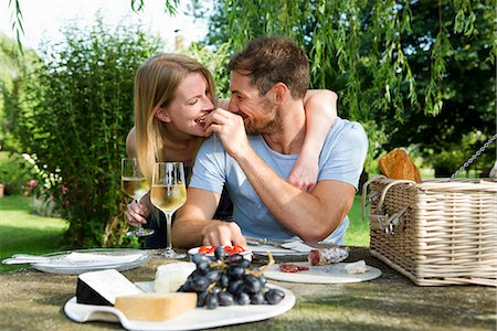 Mid adult man feeding girlfriend from picnic table in garden Stock Photo - Premium Royalty-Free, Code: 649-07803439